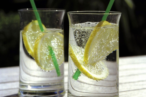 Two glasses with mineral water, lemon slices and straws standing in the sun.